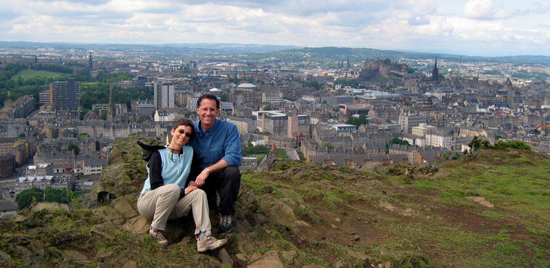 Dr. Diane Calleson and her husband Jerry pause at the end of a 70-mile trek in the Scottish Highlands. The city of Edinburgh is in the background.