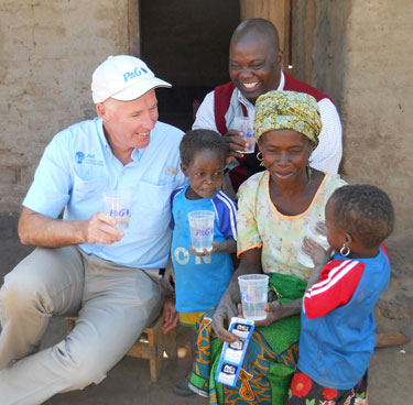 Dr. Greg Allgood (left) and Mr. Innocent Mofolo (center, back) deliver the celebratory cup of clean water to Lusiya Daniel and her family in Malawi.