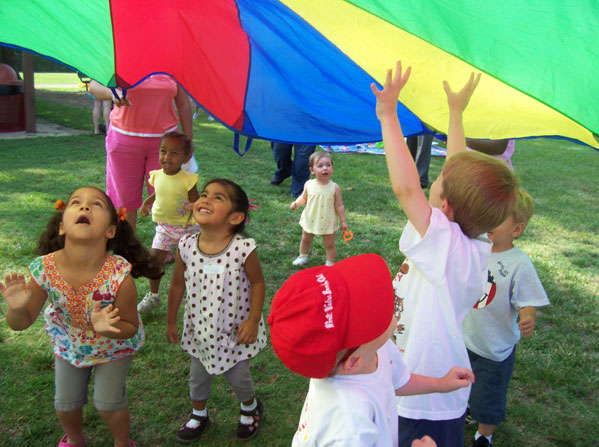 Children playing under brightly colored tent
