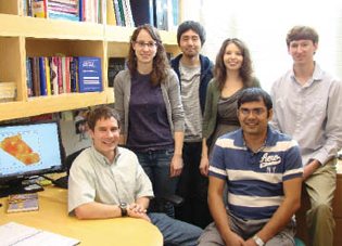 Dr. Marc Serre (seated, left) consults about a disease-mapping project with fellow researchers (l-r) Jeannette Reyes, doctoral student; Dr. Yasuyuki Akita, postdoctoral fellow; Lani Clough, master's student; and Prahlad Jat (foreground) and Kyle Messier, doctoral students. All work or study in the environmental sciences and engineering department.