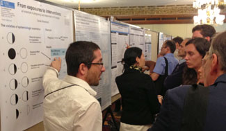 Dr. Daniel Westreich (left) discusses his prize-winning poster.