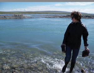 Dr. Rose Cory collects water samples at her field site in the Arctic.