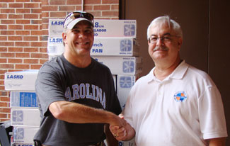 Bill Gentry (left) presents donated fans to Orange County (N.C.) Emergency Services director, Col. Frank Montes de Oca.