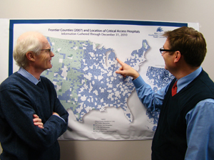 Dr. George Pink (left) and Dr. Mark Holmes review the locations of critical-access hospitals in the United States.