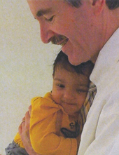 Dr. Bert Peterson holding Nikhil Gomez (photo by Anu Manchikanti Gomez)