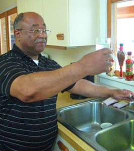 The Rev. Robert Campbell checks the water coming from the tap in his home. Most families in the area get their water from wells.