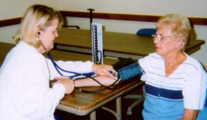 A public health nurse checks a woman's blood pressure during field work.