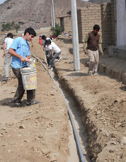 Students, with community members from Ciudad de Dios, Peru, line pipe trenches with sand to protect the pipes in the water distribution system.