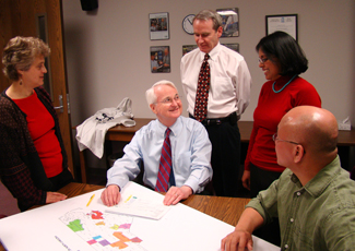 Dr. Gary Rozier (center) discusses his work in North Carolina with (l-r) project manager Leslie Zeldin; Dr. William Vann Jr., professor of dentistry; postdoctoral fellow Dr. Bhavna Pahel; and Dr. Daniel Lee