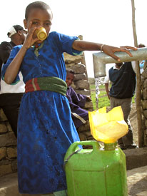 An Ethiopian girl drinks from a hand pump