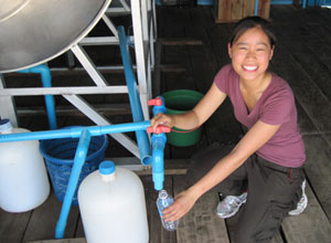 Doctoral student Alice Wang fills bottles with filtered water in Cambodia.