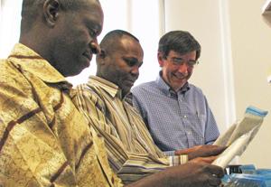 Dr. Steven Meshnick (right) works with Kashamuka Mwandagalirwa (left) and Jeremie Muwonga to sort dried blood-spot samples.