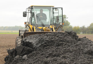 A farmer spreads sludge to fertilize his fields. Photo courtesy of Sustainable Sanitation Alliance.