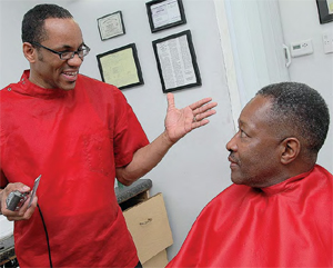 Greensboro barber Ed Hooker tells a client about the benefits of cancer screenings.