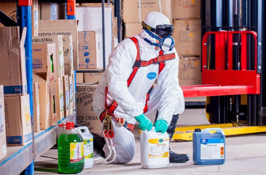 Man in white hazmat suit holding chemicals