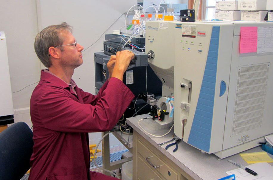 A researcher works with lab equipment.