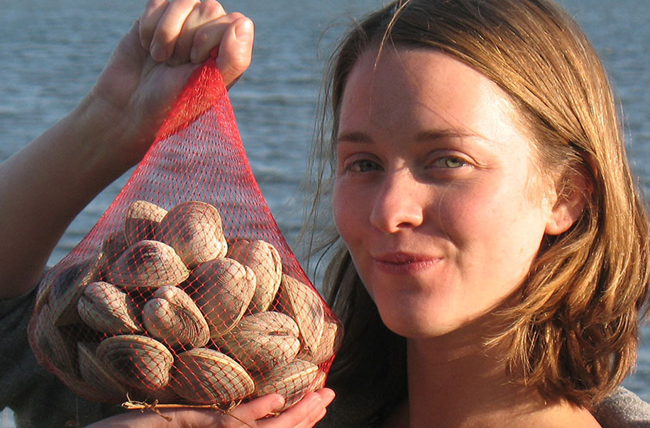 A student holds a basket of oysters.