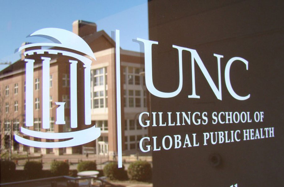 The UNC Gillings School logo pictured on a door to the building.