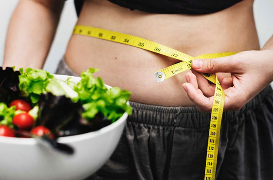 A woman measures her body circumference while holding a salad.