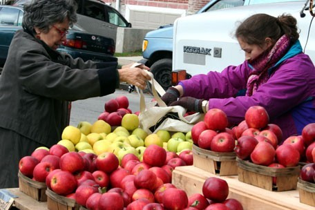 A woman purchases apples at a farmers' market.
