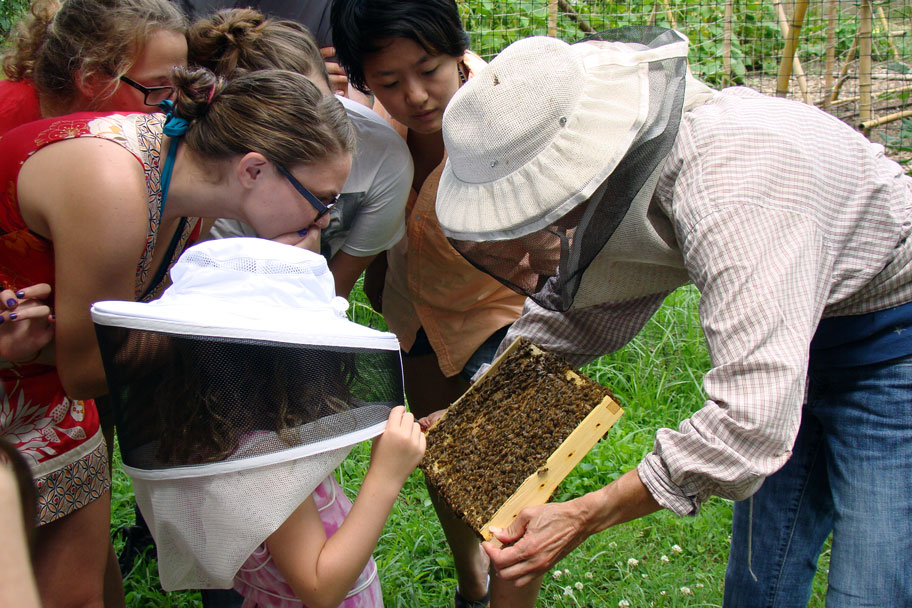 Health behavior alumna Anne Cabel (right) conducts a beekeeping workshop at the Carolina Campus Community Garden.