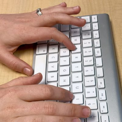 Hands type on a wireless keyboard.