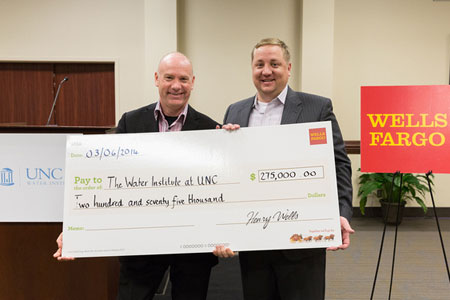 Dr. Jamie Bartram, left, accepts Wells Fargo's grant for The Water Institute's work on climate change.