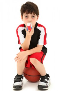 A child sits on a basketball and uses his inhaler.