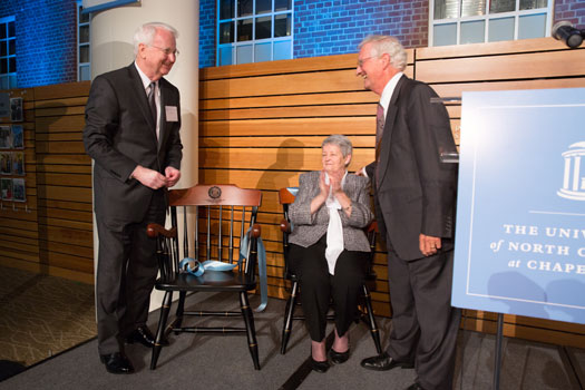 Dr. Gary Rozier (left) is acknowledged by Dr. Chet Douglass at a dinner celebrating Rozier's career. Jeanette Rozier looks on.