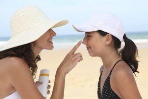 A woman applies sunscreen to a child.