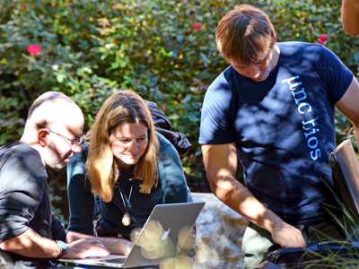 Dr. Amy Herring (center) works with two biostatistics students outside on a sunny day.