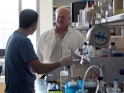 Dr. Ralph Baric works with a student in his research laboratory.