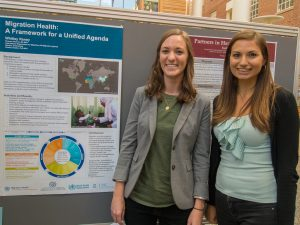 Health behavior master's students Raney Witley and Kaitlyn Brodar post beside Whitley's poster at Practicum Day, 2016.