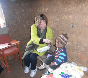 Dr. Peggy Bentley feeds a child in Peru. Taking a break from interviewing the child's mother about family feeding practices, Bentley introduces a snack prepared with an infant food grinder, a low-tech, inexpensive tool to provide young children with safe, nutritious food.