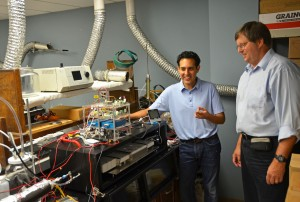 Drs. Will Vizuete (left) and Ken Sexton describe the workings of Quantaire, a portable air-sampling device they developed.