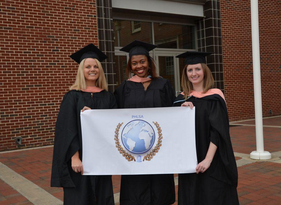 Recent graduates holding a PHLSA sign.