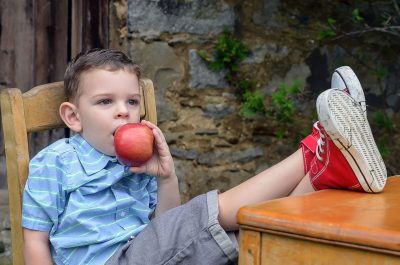 A boy holds an apple and wishes for chocolate.