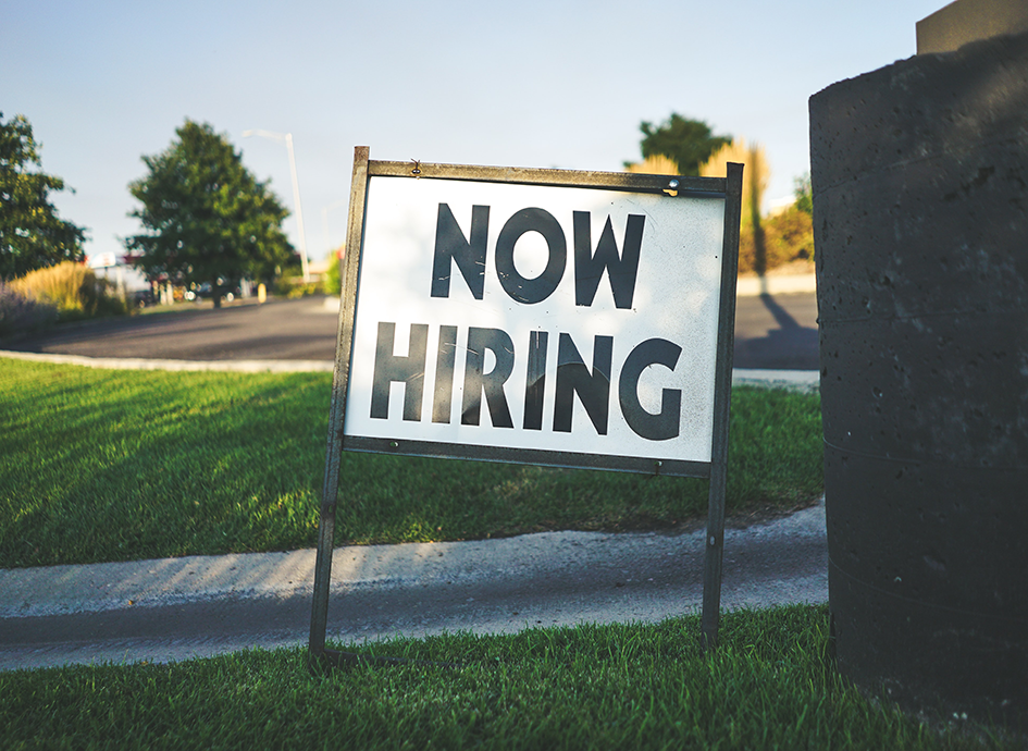 A Now Hiring sign sits in a yard.