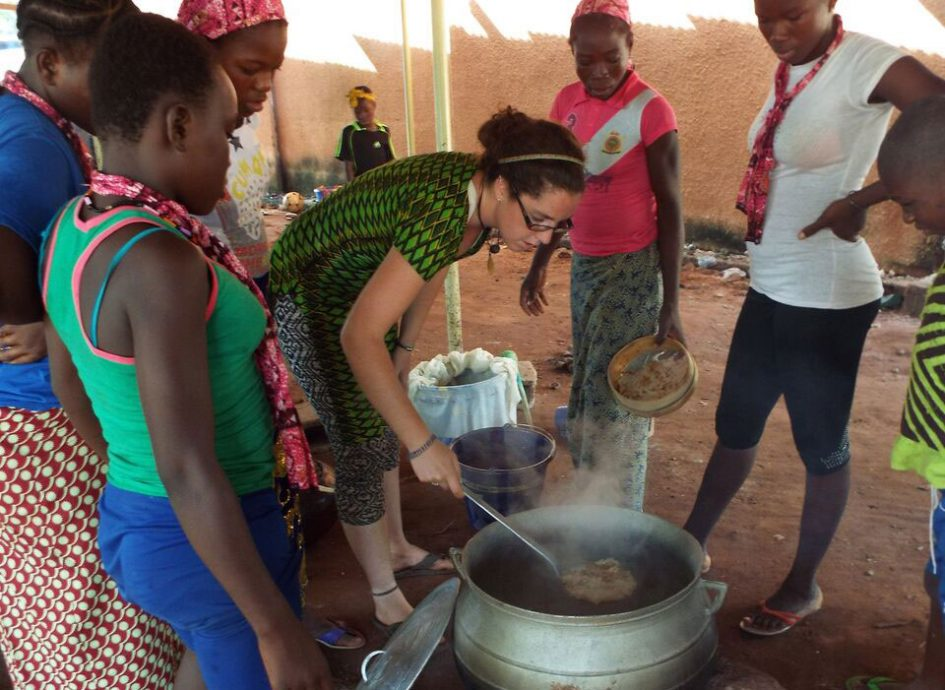 eace Corps volunteer Charlotte Lane (center) cooks with villagers in Burkina Faso. (Photo credit: Charlotte Lane)
