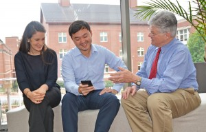 Dr. Ed Fisher (right) reviews a Peers for Progress app with student assistant Sarah Kowitt and program manager Patrick Yao Tang. (Photo by Linda Kastleman)
