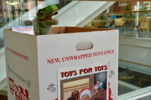 A T-Rex guards the Toys for Tots donation box.