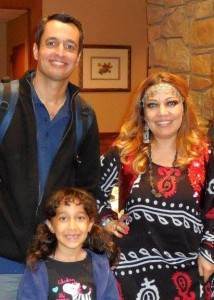 Dilshad (left) presents at a meeting of the Cary-Kildaire Rotary Club. He is accompanied by his wife (dressed in a Kurdish traditional costume) and their daughter. (Contributed photo)