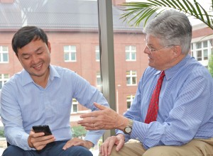 Dr. Edwin Fisher (R) speaks with Patrick Yao Tang, MPH, program manager of Peers for Progress.