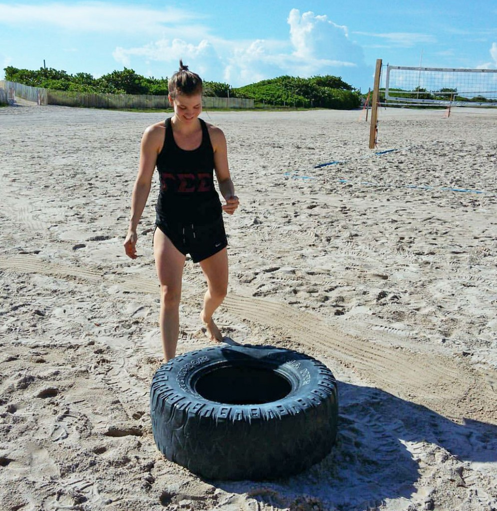 Sarah Smith flips tires on the beach.