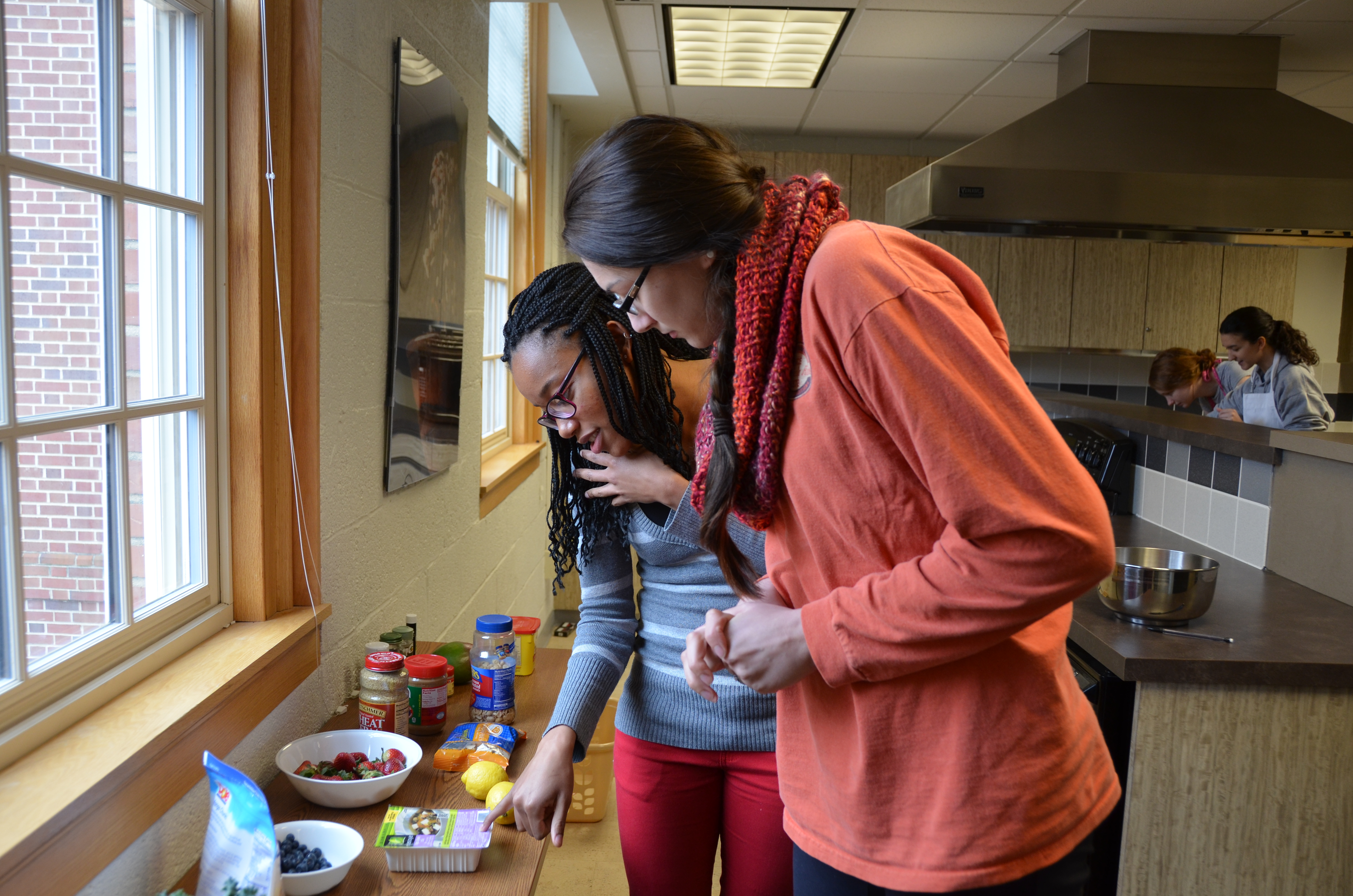 Two students confer over a healthy recipe during a nutrition class.