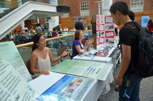 A student volunteer (left) speaks with a classmate about clean water.