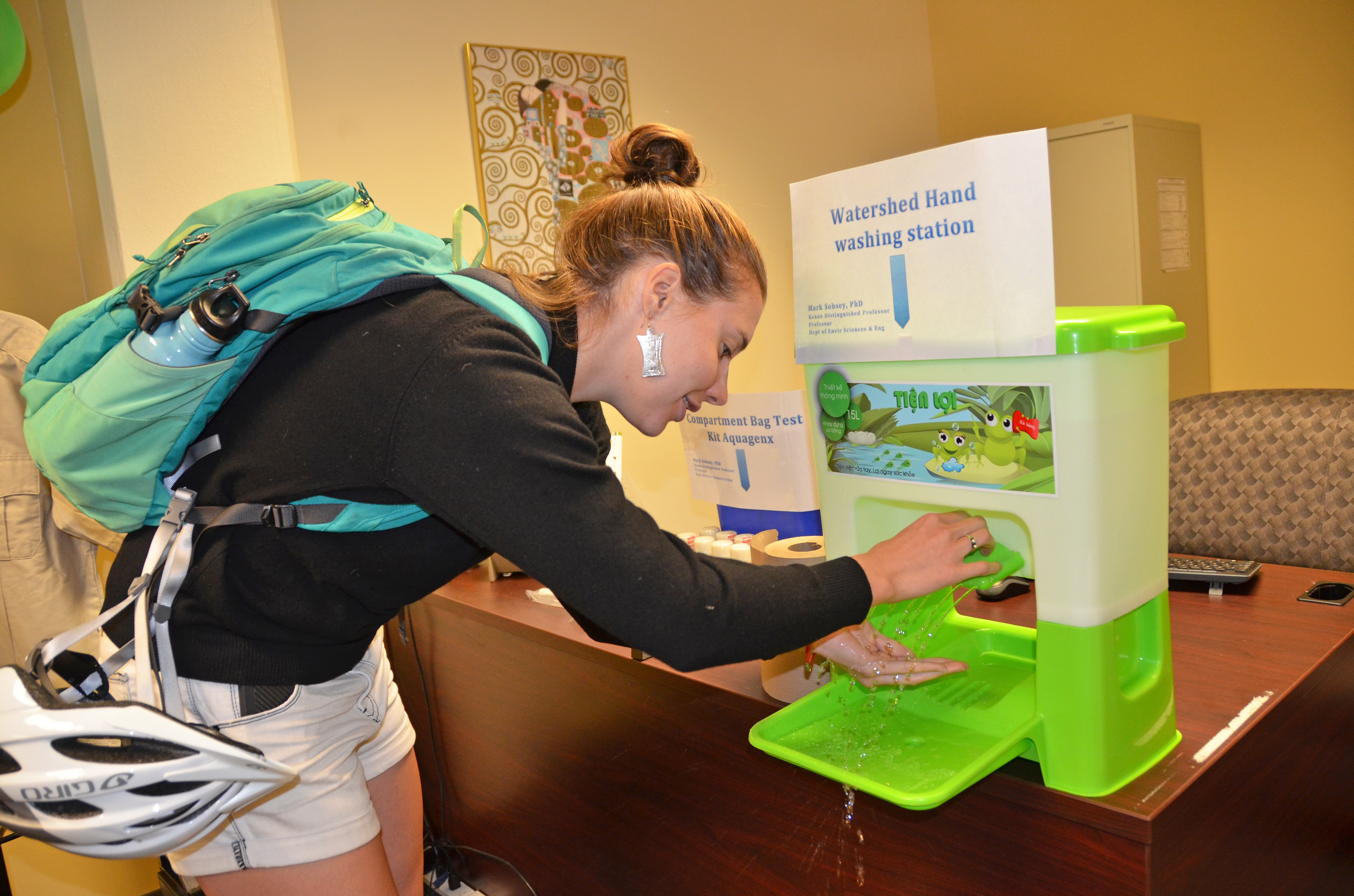 A visitor to the Gillings Global Gateway's Open House tries out a hand washing station used in the field.