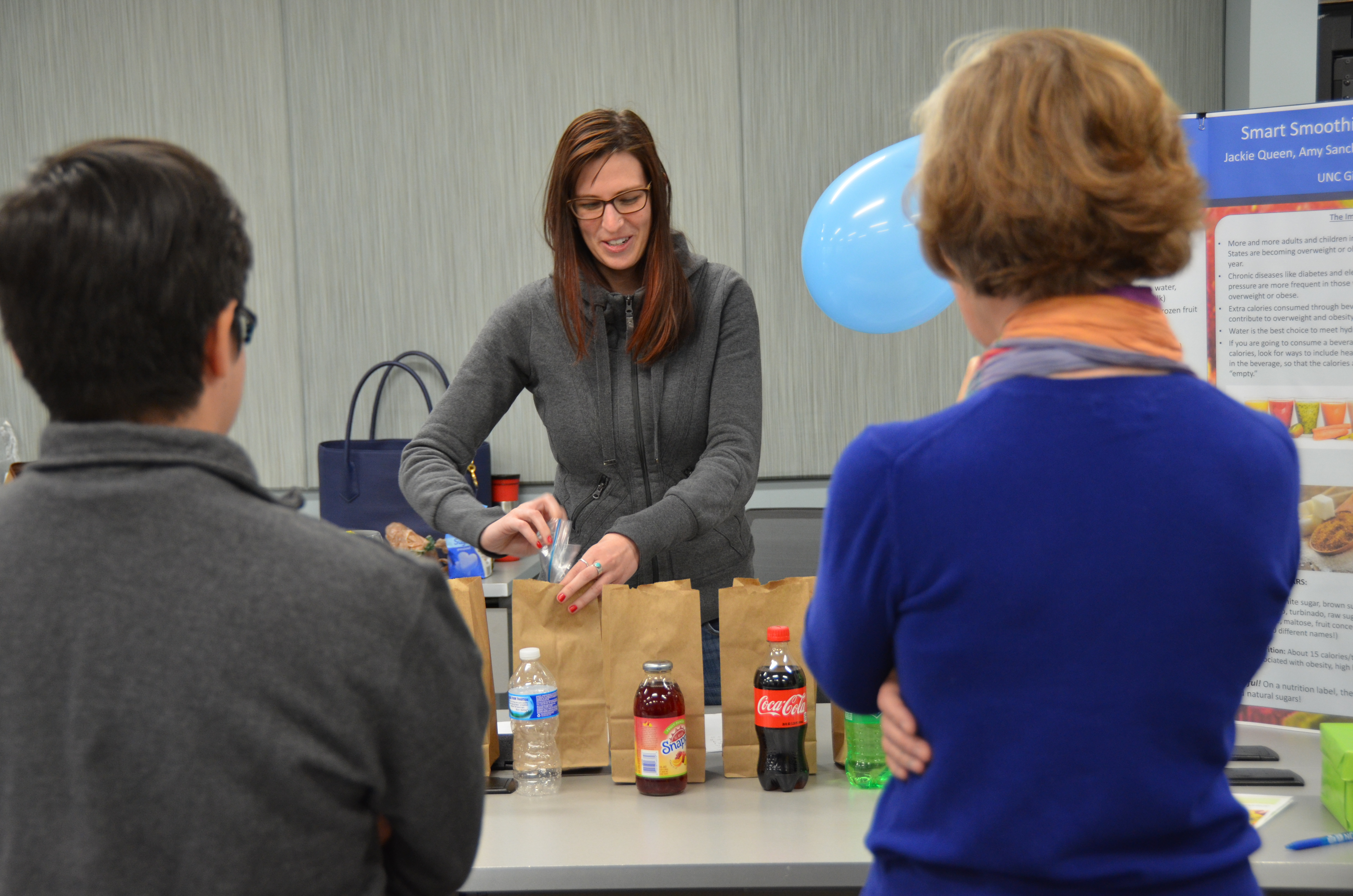 A student shows off her group's interactive nutrition display for the annual North Carolina Science Festival.