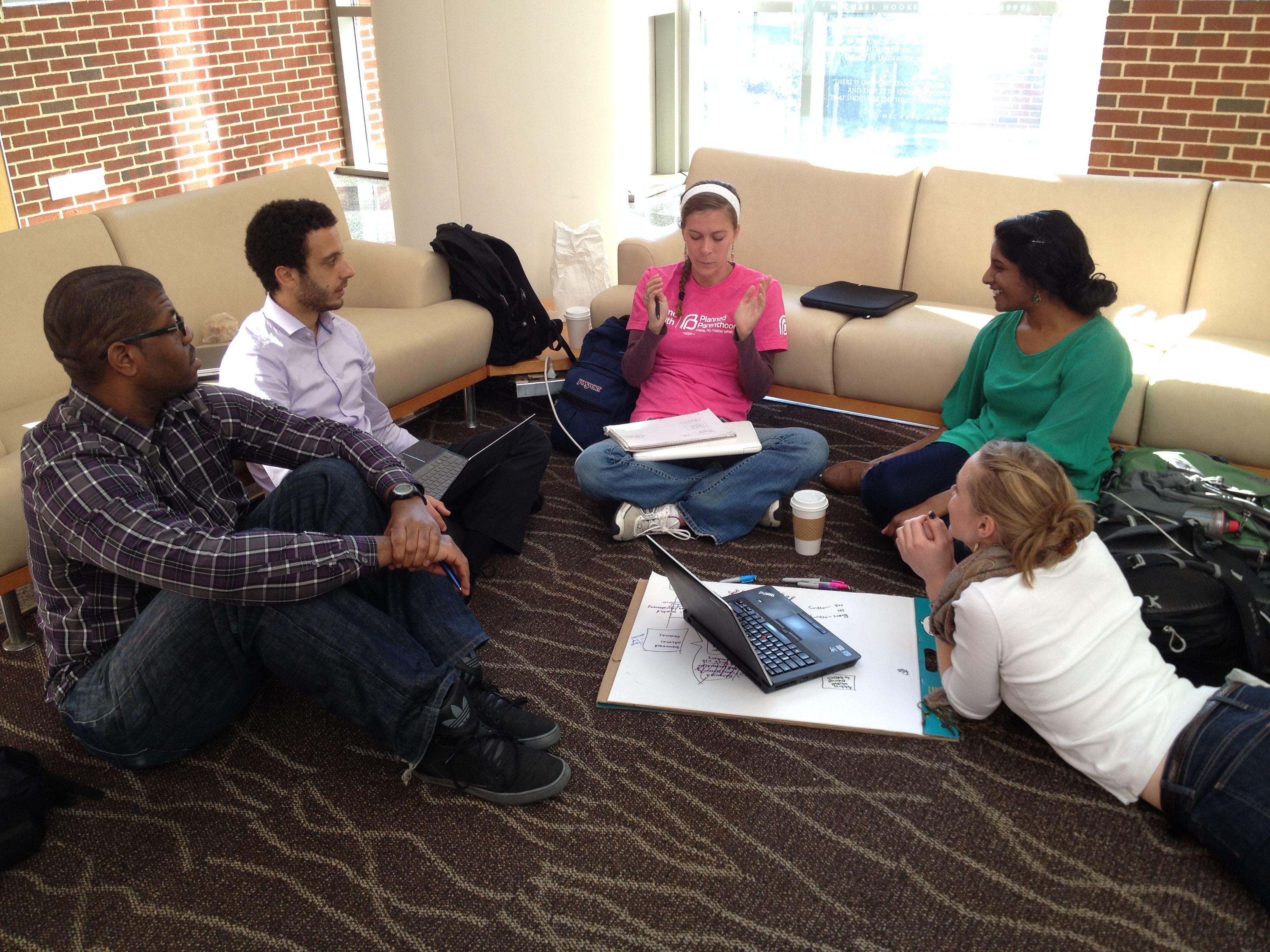 Classmates from the health behavior department brainstorm project ideas in Armfield Atrium.