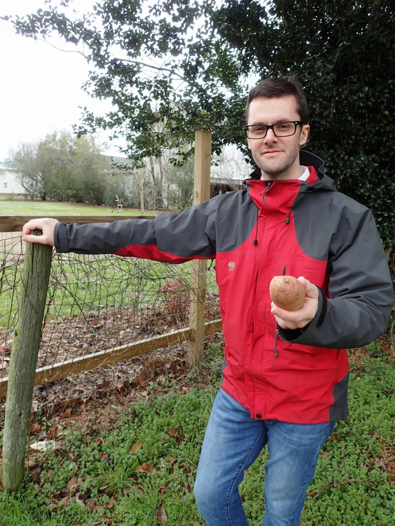 Jed Hinkley holds a sweet potato, one product of the farms and markets he often visits. (Contributed photo)